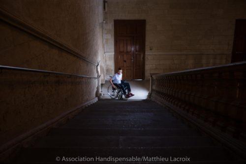 Photo d'une personne en situation d'handicap en bas d'un escalier. Illustration des problèmes d'accessibilité.