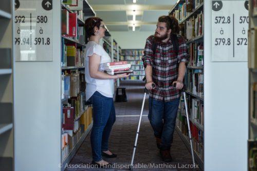 Personne avec des béquille dscutant avec une bibliothécaire dans une bibliothèque. Photo illustratant les problèmes d'accessibilité.